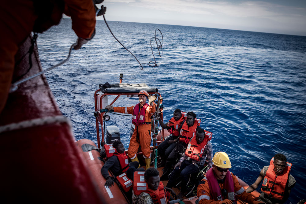 A small lifeboat carrying six refugees approaches the Vos Hestia. A rope is being tossed to the crewmember on the life boat as it prepares to unload the rescued passengers onto the Vos Hestia.