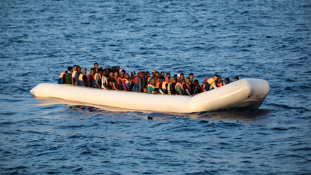 Dozens of people are crowded into a white inflatable boat floating in the dark blue sea. Some are wearing life jackets.