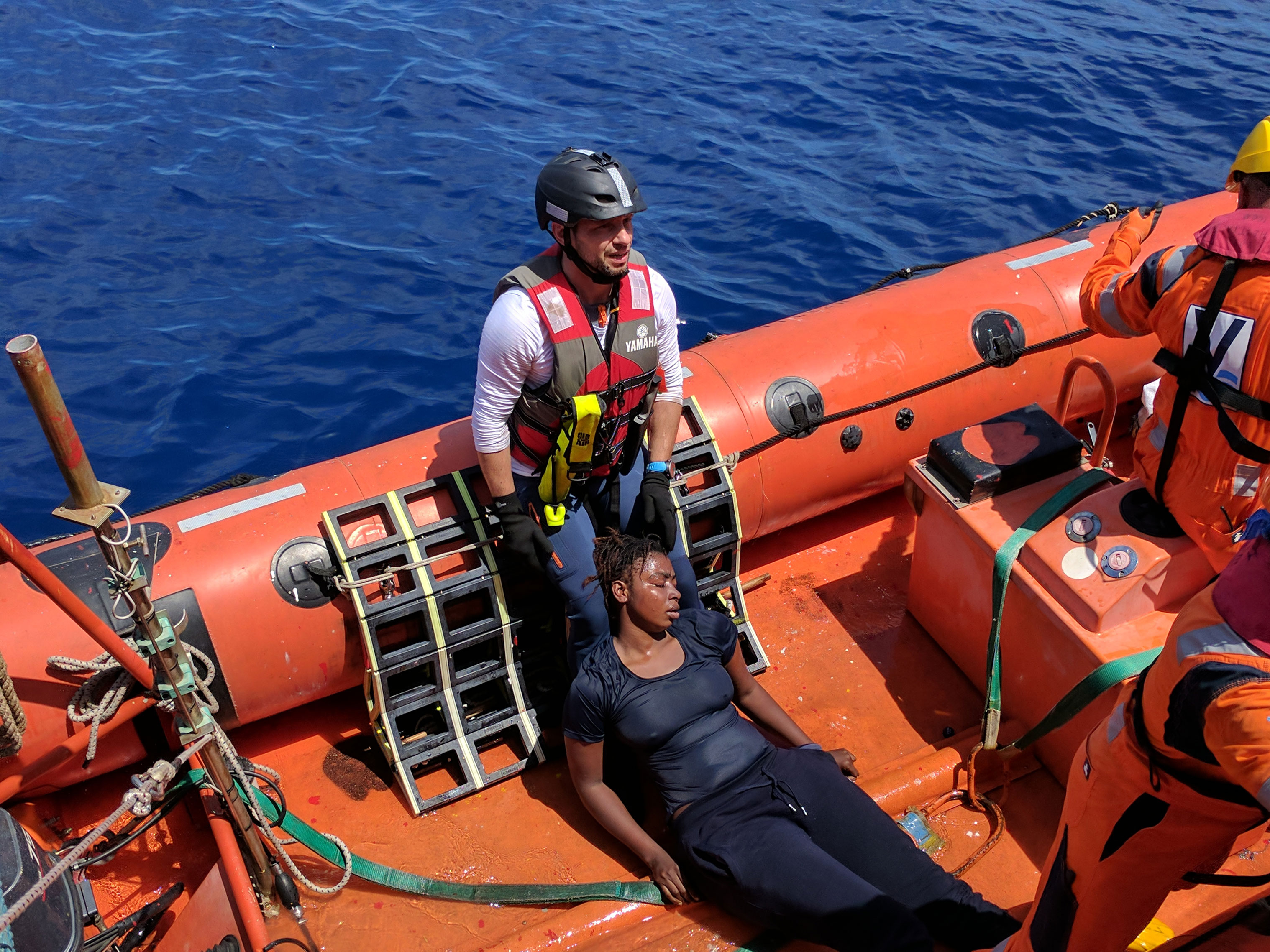 A woman wearing blue clothes, visibly wet from the ocean, slumps against the legs of one of the crewmembers after being pulled into the rescue dinghy.